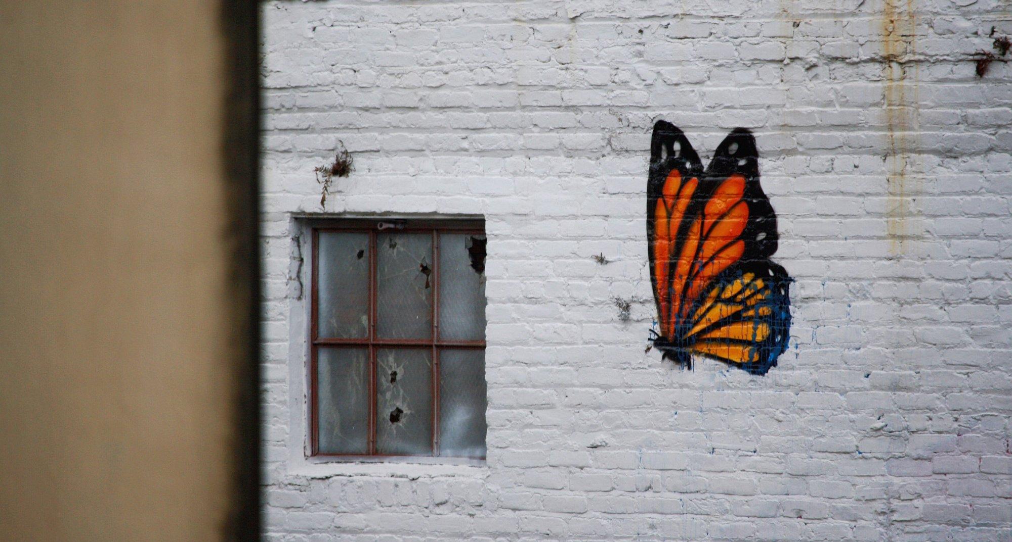 Streetart: Ein bunter großer Schmetterling auf einen schäbigen weißen Hauswand